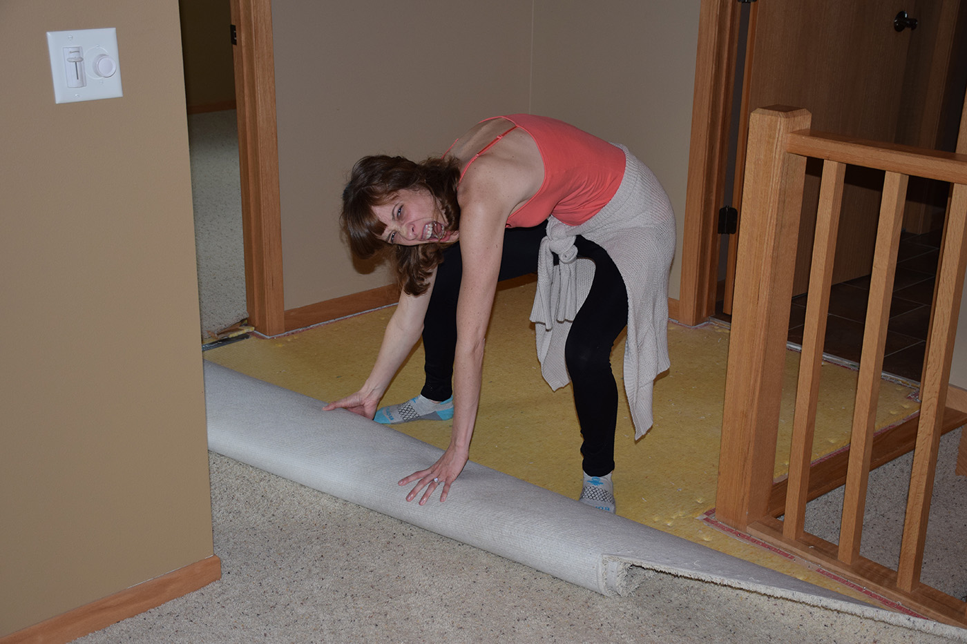 Meghan tearing up carpet to lay Hardwood Flooring